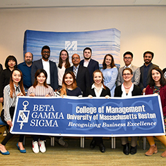 Honor students holding the Beta Gamma Sigma banner.