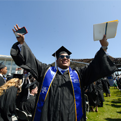 Graduate with arms outstretched