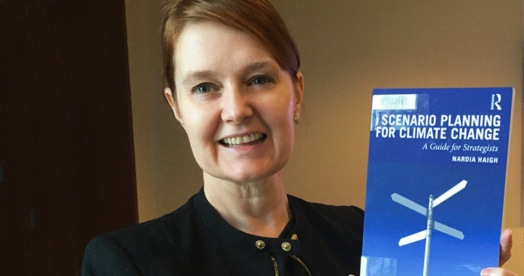 Professor Nardia Haigh holds up her book, Scenario Planning for Climate Change.