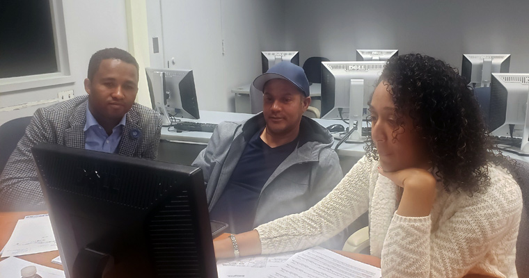 Two volunteers helping a man with his taxes