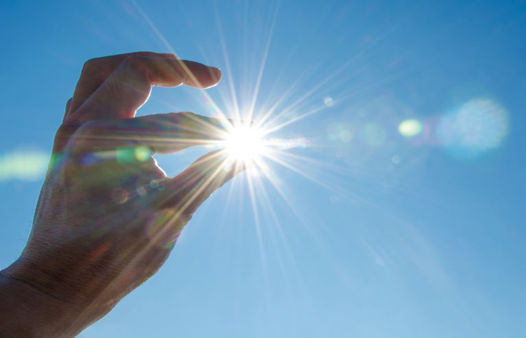 hand with flare of light held between fingers